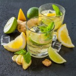 48447682 - ginger lemonade and ingredients, dark stone background, copy space