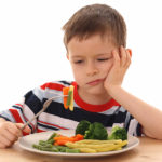 5-6 years old boy and plate of cooked vegetables isolated on white